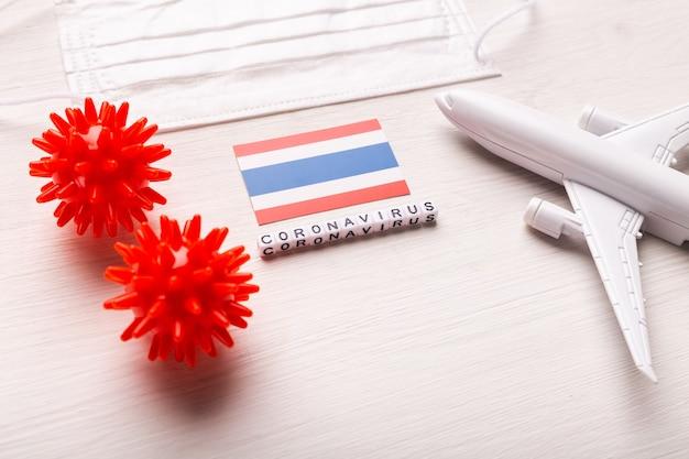 Modelo de avião e máscara facial e bandeira tailândia. pandemia do coronavírus. proibição de voos e fronteiras fechadas para turistas e viajantes com coronavírus covid-19.