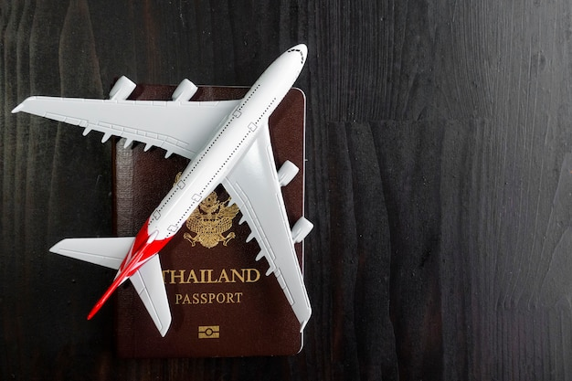 Modelo de avião e passaporte na mesa de madeira, conceito de viagens prontas