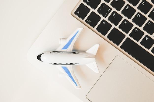 Modelo de avião fica em um laptop. revisão da programação de voos on-line. vista do topo.