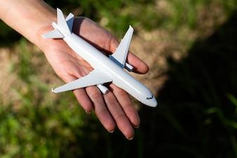 Modelo de avião na mão no céu ensolarado. Conceitos de viagem, transporte