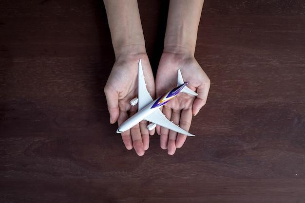 Modelo de avião rodeado de mãos