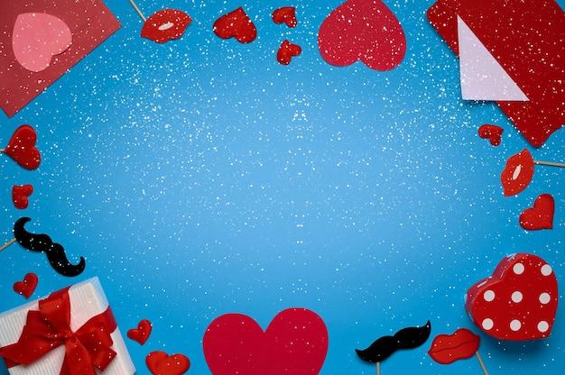 Modelo de banner de dia dos namorados com envelope vermelho, presente de dia dos namorados, decoração de lábios em fundo azul com espaço de cópia. vista superior, configuração plana