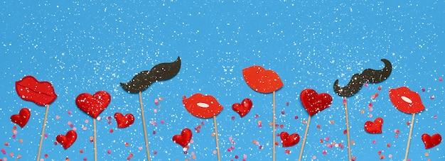 Modelo de banner de dia dos namorados com lábios vermelhos, presente de dia dos namorados, decoração em fundo azul com espaço de cópia. vista superior, configuração plana