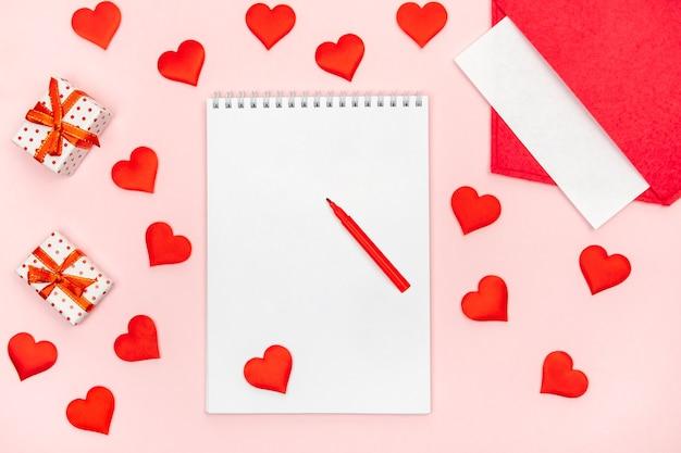 Modelo de bloco de notas flatlay com caneta hidrográfica com envelope vermelho com corações e presentes