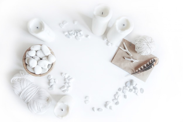 Modelo de boho branco com velas, fio de algodão, penas e seixo do mar branco sobre a mesa.