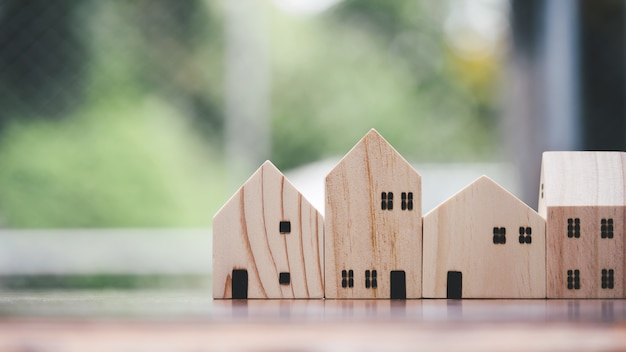 Modelo de brinquedo de madeira de casa na mesa da escrivaninha marrom, close-up.