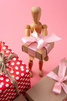 Modelo de brinquedo de madeira segurando presentes. cartão de férias para dia dos namorados e dia das mulheres