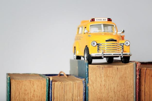 Modelo de brinquedo de ônibus escolar amarelo e livros antigos.