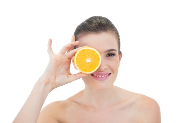 Modelo de cabelo castanho natural alegre escondendo os olhos com uma laranja metade