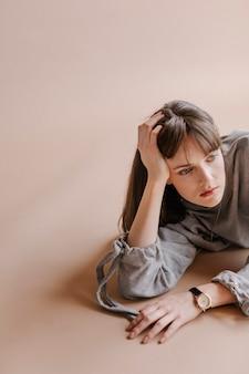 Modelo de cabelo castanho posando em um estúdio