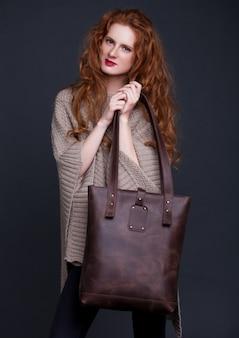 Modelo de cabelo vermelho, segurando o saco de couro escuro grande em fundo escuro. menina vestindo jumper.