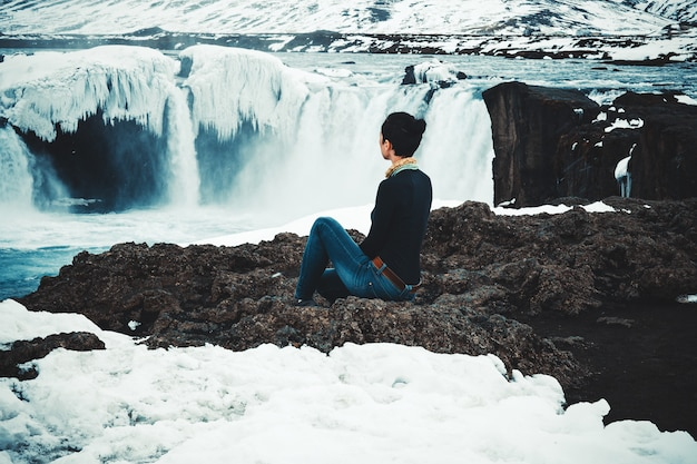 Modelo de cabelos escuro está posando sentado com uma cachoeira