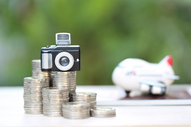 Modelo de câmera na pilha de moedas dinheiro e avião no passaporte