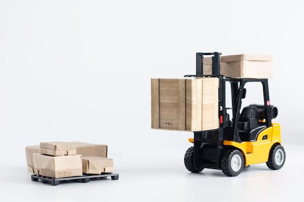 Modelo de caminhão de empilhadeira em miniatura carregando caixa de papelão isolada