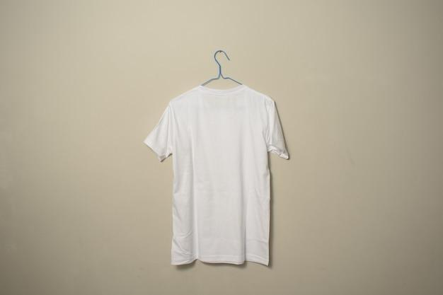 Modelo de camiseta branca em branco no cabide na vista lateral traseira do plano de fundo da parede