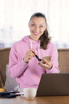 Modelo de capuz rosa fazendo maquiagem funciona com computador portátil