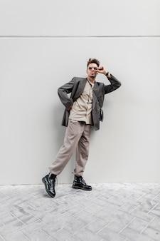 Modelo de cara de empresário na moda em roupas de aparência elegante com óculos de sol caminha na rua perto de uma parede cinza. moda casual masculina, estilo e beleza