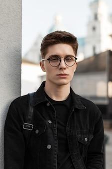 Modelo de cara jovem e bonito com óculos em roupas jeans pretas da moda na cidade