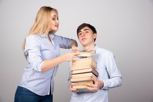 Modelo de cara morena de pé e carregando uma pilha de livros perto de uma mulher loira