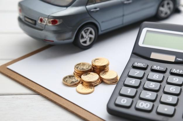 Modelo de carro, calculadora e moedas na mesa branca