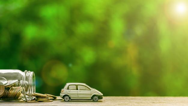 Modelo de carro cinza em miniatura e moedas na tabl de madeira