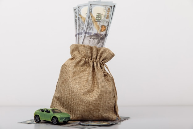 Modelo de carro com bolsa de dinheiro em fundo branco.