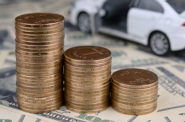 Modelo de carro de brinquedo nas pilhas de moedas de ouro encontra-se em muitas notas de dólar
