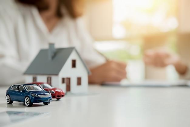 Modelo de carro e casa com agente e cliente discutindo para contrato para comprar