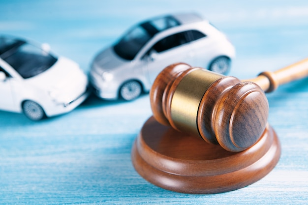Modelo de carro e martelo. ação judicial ou seguro contra acidentes, processo judicial.