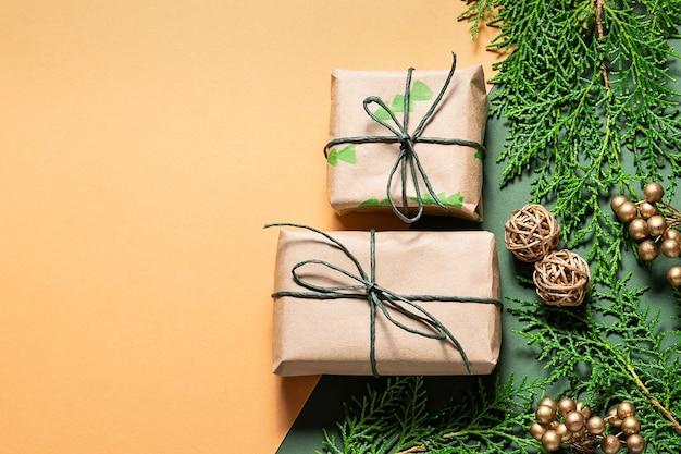 Modelo de cartão de natal com caixas de presente em papel artesanal, galhos de árvores de abeto e decoração dourada
