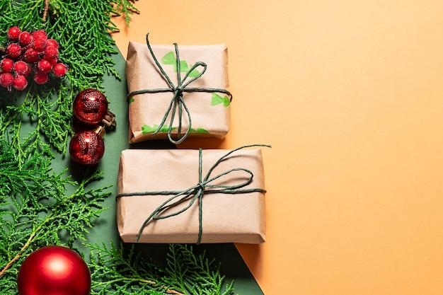 Modelo de cartão de natal com caixas de presente em papel artesanal, galhos de árvores de abeto e decoração em vermelho brilhante