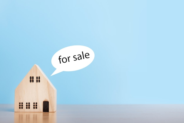 Modelo de casa à venda em fundo azul. conceito imobiliário de casa de família, seguros e investimento imobiliário. copie o espaço.