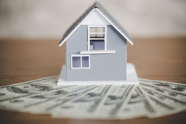Modelo de casa clássica em dólar americano na mesa de madeira