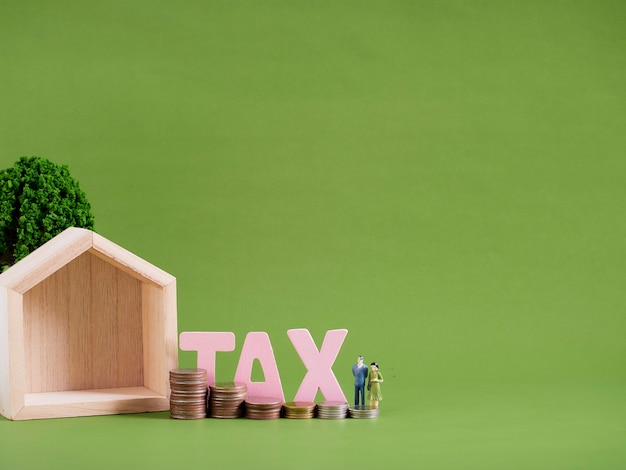 Modelo de casa com a palavra imposto, pessoas em miniatura e moedas sobre fundo verde. espaço para texto