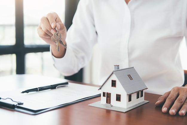 Modelo de casa com agente imobiliário e cliente discutindo para contrato para comprar casa