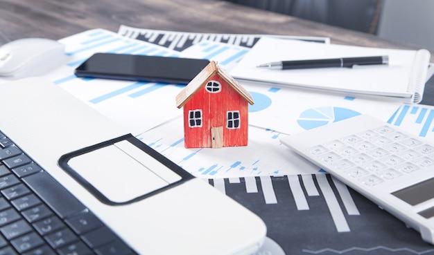 Modelo de casa com calculadora, gráficos, caneta, bloco de notas, smartphone.