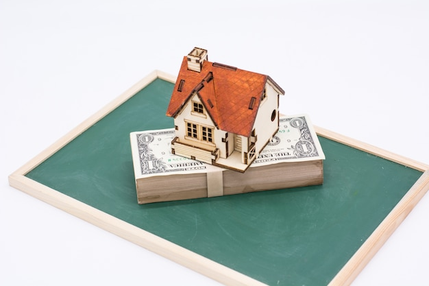 Modelo de casa com dólar na placa verde, conceito de negócio imobiliário