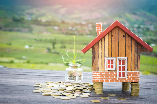 Modelo de casa com moedas na mesa de madeira no fundo desfocado