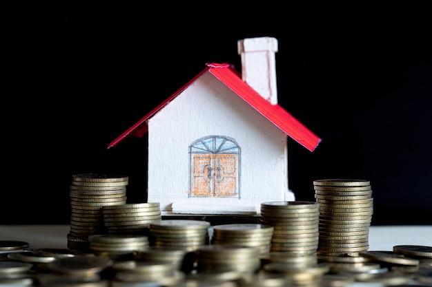 Modelo de casa com moedas na mesa de madeira