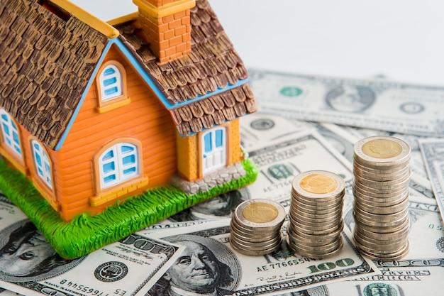Modelo de casa com muitas moedas, poupar dinheiro para o conceito de finanças e investimento