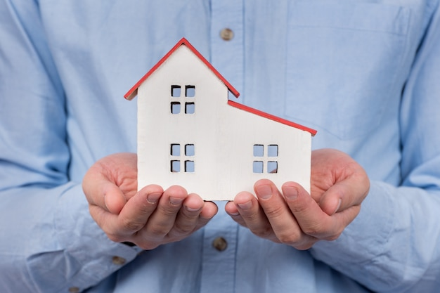 Modelo de casa de brinquedo nas mãos masculinas. compra de casa, conceito de hipoteca