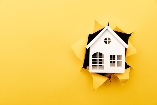 Modelo de casa de madeira branca através de um buraco de papel amarelo.
