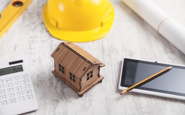 Modelo de casa de madeira com capacete e tablet.