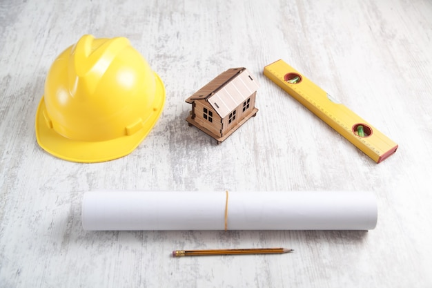 Modelo de casa de madeira com capacete, nível, documento e lápis.
