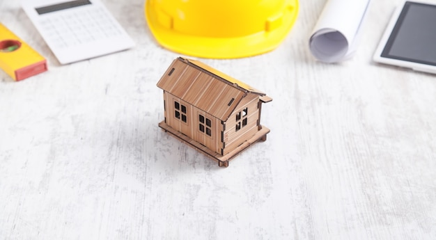 Modelo de casa de madeira com capacete, tablet, calculadora, nível e documento.