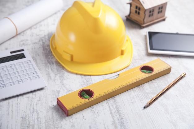 Modelo de casa de madeira com capacete, tablet e outros objetos.