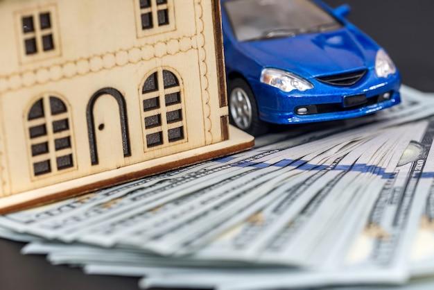 Modelo de casa de madeira com carro de brinquedo e pilha de dólares