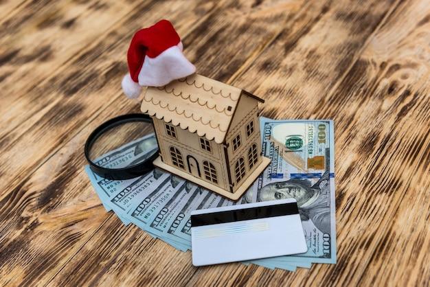 Modelo de casa de madeira com chapéu de papai noel e notas de dólar