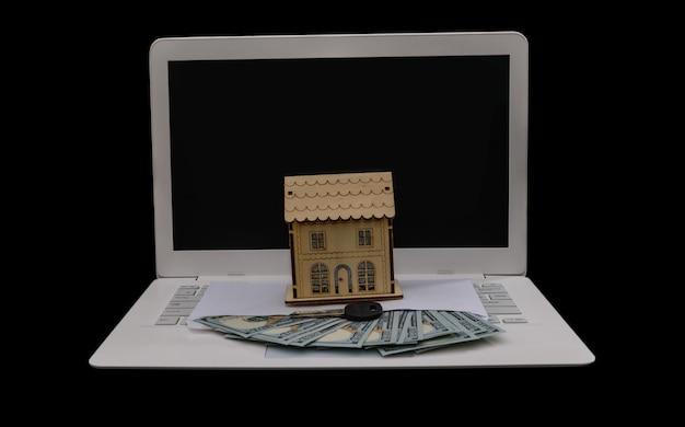 Modelo de casa de madeira com chave e dólares no teclado do laptop