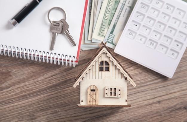 Modelo de casa de madeira com chaves, calculadora, dinheiro, caneta e bloco de notas.